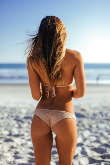 slim escort with long hair on beach looking out over sea