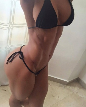 Diane escort showing off muscular physique in black string bikini