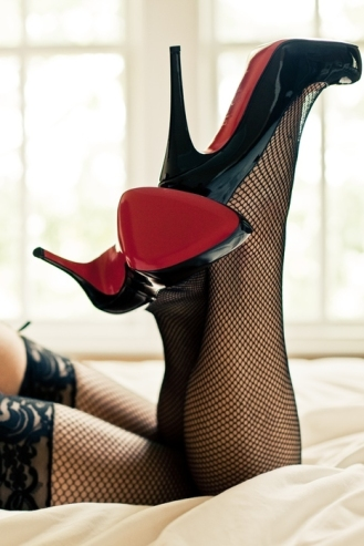 escort wearing fishnet stockings and black patent high heels with red soles